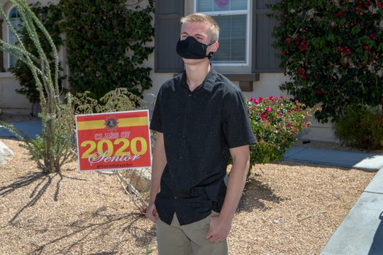 Palm Desert High School senior Connor Sweeney, 18, stands outside his Palm Desert, Calif., home on Wednesday, April 15, 2020. To help lift spirits, the PDHS Senior Class of 2020 committee distributed yard signs to graduating seniors.