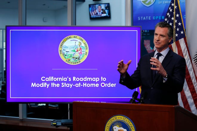 Gov. Gavin Newsom discusses an outline for what it will take to lift coronavirus restrictions during a news conference at the Governor's Office of Emergency Services in Rancho Cordova on Tuesday.