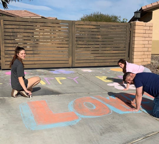 Elle and Misha Jarecki design a chalk art message with their dad, Joey. Although the activity was inspired by a mother-daughter organization, with so many families obeying stay-at-home orders, others got involved.