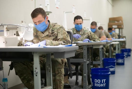 Specialist Mavrick Graves with the Army's 7th Special Forces Group at Eglin Air Force Base sews the face and backing for protective masks in the parachute rigger shed on the group's compound. The riggers make nearly 500 masks per day which are being sent to military hospital workers and other military and Department of Defense personnel. The soldiers are wearing completed masks.