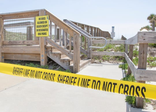 Police tape blocks shore access as the beaches remain closed due to the coronavirus pandemic in Pensacola on Wednesday, April 15, 2020.