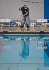 Heath Williams of Premier Pools and Spas works to complete the pool replastering and renovation project at Washington High School on Tuesday, April 15, 2020.