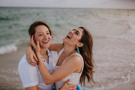 Stephanie Hartman and Christina Ingrassia smile during a photo session on Pensacola Beach, a place they both fell in love with and wanted to get married at. Coronavirus has delayed their nuptials, but the New Orleans couple is taking the rescheduling in stride.