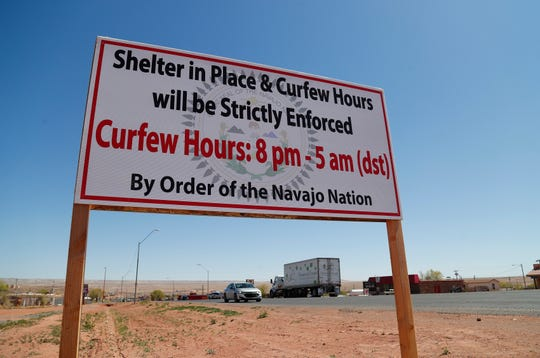A sign in Tuba City, Ariz. reminds residents of the curfew hours in place to fight against the coronavirus April 14, 2020. The Navajo Reservation has seen a spike in COVID-19 cases.