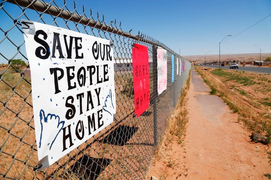 Signs on a fence in Tuba City, Arizona, remind residents to shelter in place to fight against the coronavirus on April 14, 2020. The Navajo Reservation has seen a spike in COVID-19 cases.