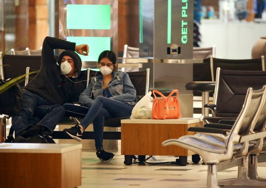 Two passengers wearing face coverings wait for a flight at Phoenix Sky Harbor International Airport on Tuesday, April 14, 2020, in Phoenix. The coronavirus outbreak has caused a significant decrease in air travel.