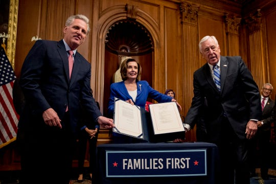 House Speaker Nancy Pelosi of Calif., House Minority Leader Kevin McCarthy of Calif., left, and House Majority Leader Steny Hoyer of Md., right, holds up the Coronavirus Aid, Relief, and Economic Security (CARES) Act after Pelosi signed it on Capitol Hill, Friday, March 27, 2020, in Washington. The $2.2 trillion package will head to head to President Donald Trump for his signature. (AP Photo/Andrew Harnik)