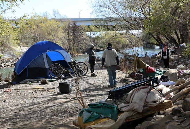 20 year resident of Reno James Fisher, middle, walks back to his tent at a homeless encampment near the Kietzke Lane bridge over the Truckee River on April 15, 2020.