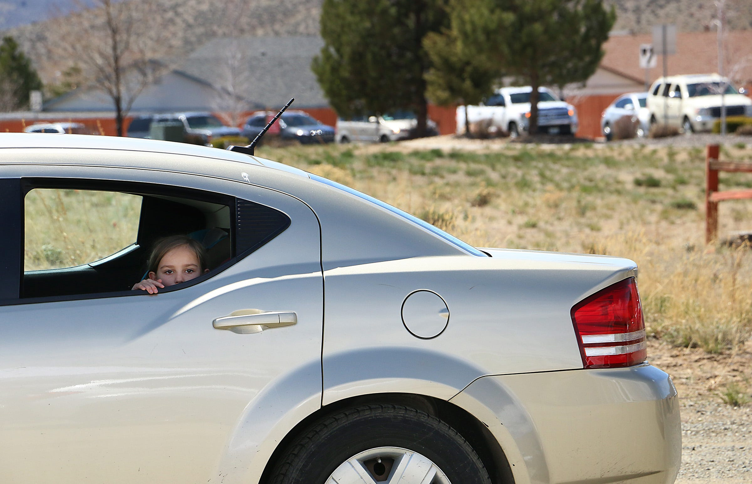 A child looks out the window of her family's car as hundreds of people line up to receive food from the Food Bank of Northern Nevada at the Cold Springs Family Center north of Reno on April 15, 2020.