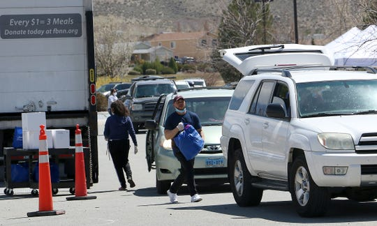 Volunteers distribute bags to the hundreds of people lining up to receive food from the Food Bank of Northern Nevada at the Cold Springs Family Center north of Reno on April 15, 2020.