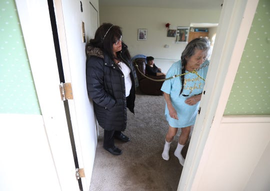 Nancy Moreno of Irondequoit talks to her  mother, Maria Rodriguez, who was walking around the living room after having a snack on Wednesday, April 15, 2020.  Moreno shares care taking responsibility of her parents Maria Rodriguez and Angel Moreno with her sister, Carmen Moreno, seated.  The homemade ropes in her parents' apartment in Irondequoit help keep Maria Rodriguez from leaving a room or entering another room.  The rope system was created by Angel Moreno.