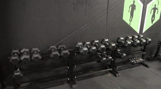 Most of the dumbbells at Hybrid Farm have been taken by members to use at home Wednesday, April 15, 2020, in St. Cloud.
