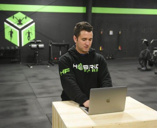 Ryan Avery, owner of the gym Hybrid Farm, shows what his new work station looks like Wednesday, April 15, 2020, in St. Cloud.
