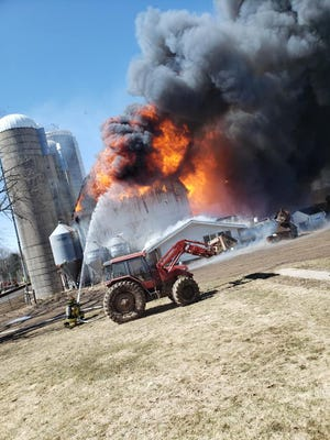 A firefighter works to put out the flames coming from the Klussendorf's dairy farm in Medford, Wisconsin Sunday, April 5, 2020.
