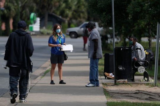 Kearney Center employees provide case management to a group of people sleeping across the street from the shelter as they work to move folks into non-congregate shelters Tuesday, April 14, 2020.