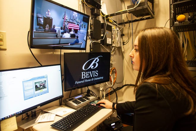 Breanna Green, a funeral director and embalmer at Bevis Funeral Home, controls the live stream feed of a funeral, Friday, April 10, 2020.