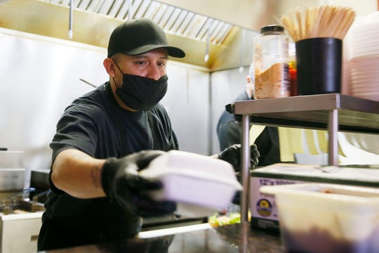 Panda Burger cook Thomas Rodriguez prepares burgers for their $5 burger special Wednesday, April 15, at 10780 Pebble Hills Blvd. in El Paso. Some restaurants in El Paso have had to temporally close with COVID-19 but others have been able to keep their workers employed by using multiple platforms to deliver food.