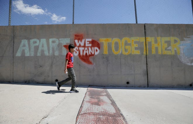 "Kevin Canales walks past a newly created chalk mural after picking up his lunch Tuesday, April 14, 2020, at Wiggs Middle School. ""Apart we stand together"" has become a trending hashtag on social media."