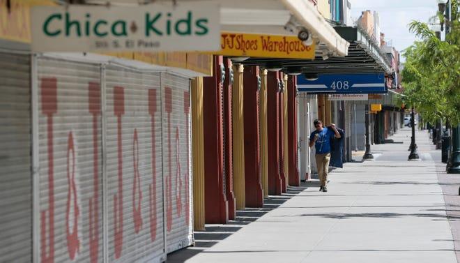 """Un hombre camina por una calle desierta en El Paso en abril de 2020 en el centro de la ciudad.  La mayoría de las empresas a lo largo de la calle comercial normalmente concurrida estaban cerradas para unirse a la """"quédate en casa, trabaja seguro"""" pedido."""
