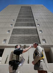 El Paso County Sheriff's Deputy Alonso Garcia takes attorney Brock Benjamin's temperature Tuesday before he enters the El Paso County Jail. All staff and visitors to the jail are being screened before entering and masks are mandatory inside the facility. On-site visitation for inmates at the Downtown jail and the Jail Annex Facility has been suspended until further notice due to the coronavirus pandemic.