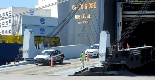 The Port of Hueneme was bustling Wednesday, with workers unloading foreign cars and containers of bananas off ships. Port officials expect a significant slowdown of auto imports in coming weeks because of the worldwide coronavirus pandemic.