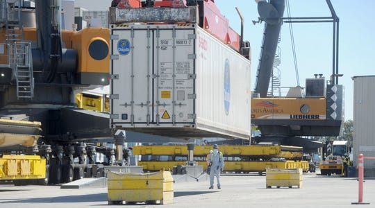 Crane operators along with workers in the ground unload bananas Wednesday at the Port of Hueneme. While other goods may slow at the port, banana shipments are expected remain the same.