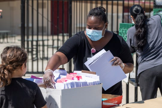 Treatment Nurse Berta Johnston hands out enrichment packets at Divisadero Middle School on Tuesday, April 14, 2020. The school was one of Visalia Unified's distribution points for grab-and-go meals along with curriculum packets.