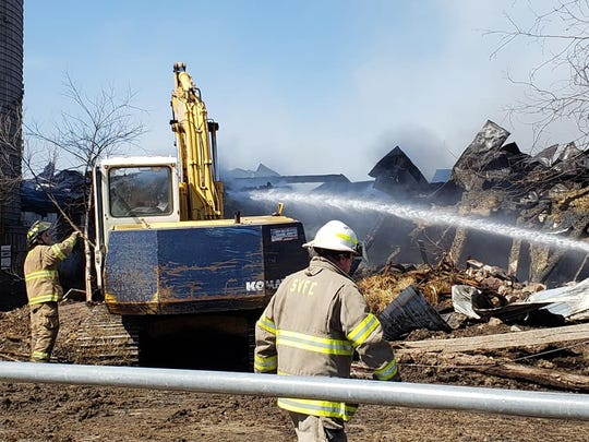 Firefighters work to put out a fire at the Klussendorf's farm in Medford Sunday, April 5, 2020.