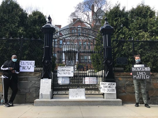 Protesters, including Hilary Whitney, right, stand outside the Governor's Mansion in Albany, N.Y., urging Gov. Andrew Cuomo to free more people from prison as COVID-19 continues its spread.