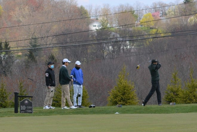 A foursome tees off Wednesday on the 10th hole at Philip J. Rotella Golf Course in Haverstraw, N.Y. The municipal course remains the only local facility to stay open for play during a statewide shutdown.
