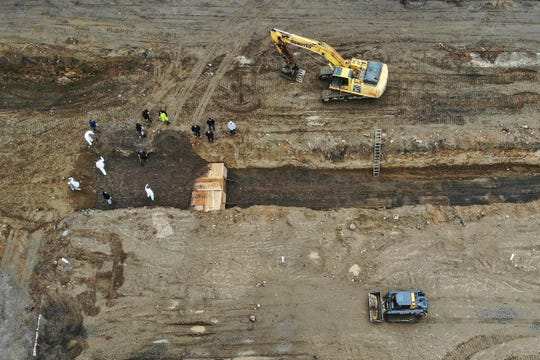 Bodies are buried in a trench on Hart Island, Wednesday, April 8, 2020, in the Bronx borough of New York.  (AP Photo/John Minchillo)
