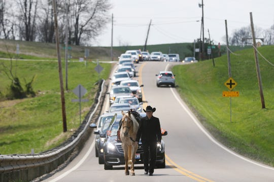 """Ruth Sunkle leads Daisy at the head of the funeral procession for Marion """"Junior"""" Hatfield as it makes its way toward New Hope Cemetery near Adamsville on Wednesday."""