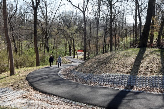 Kathy Bradshaw, left, and Cris Reed climb the hill leading from the as-yet-incomplete bridge over Joe's Run on the Joe's Run Recreational Trail. The Muskingum Valley Park District is expecting the bridge to be completed in June.