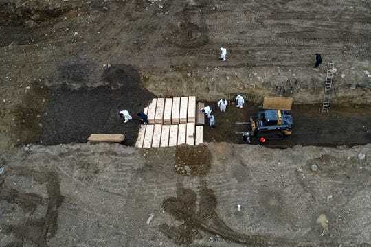 In an April 9, 2020, photo, workers wearing personal protective equipment bury bodies in a trench on Hart Island in the Bronx borough of New York.