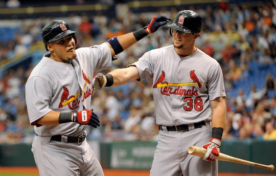 Former St. Louis Cardinals teammates Yadier Molina, left, celebrates at the plate with Mark Hamilton after hitting a solo home run.