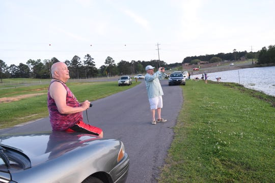 Jackson Sleet (left) and John Foster Gunter, both members of the Cenla Sunset Photographers Club, visit as they take photos of the sunset at Lake Buhlow in Pineville earlier last month.