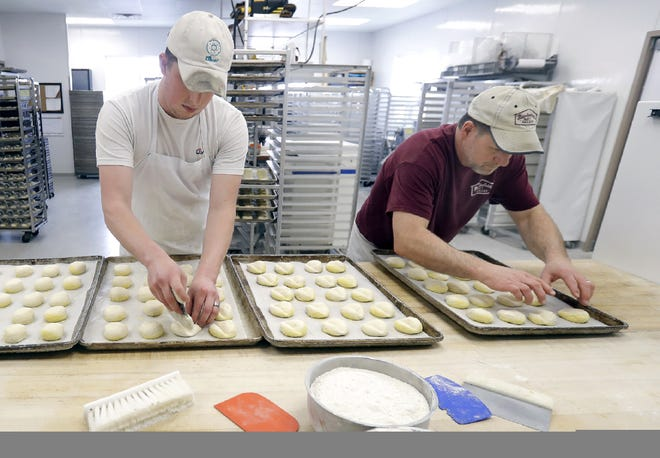 JT Heenan, left, and Jerry Manderfield prepare trays of bun dough at Manderfield's Home Bakery in Darboy. Manderfield's will reopen that location to the public on Wednesday.