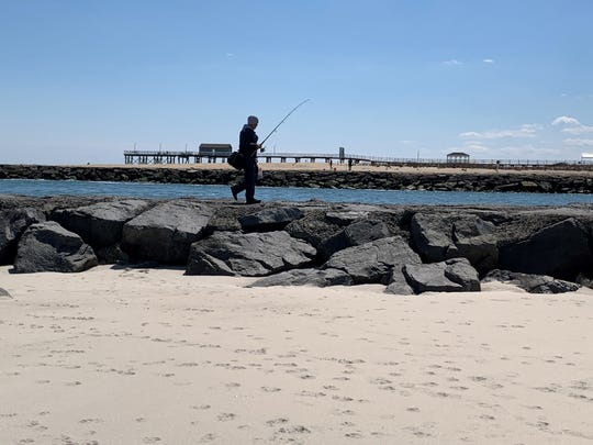 A fisherman walks along the Shark River Inlet on Wednesday, April 15, 2020.