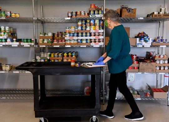 Carla McDonald gathers items for an order at Christian Service Center on Wednesday. The food pantry there is open three times a week.