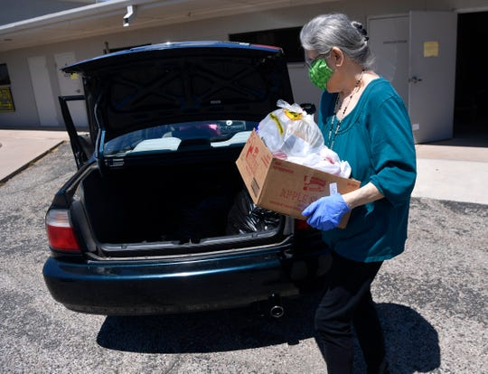Carla McDonald carries a box of food to a client's car Wednesday at Christian Service Center.