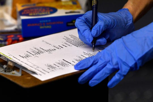 Going down a list, Carla McDonald checks off items as she fills an order for a client at Christian Service Center on Wednesday.