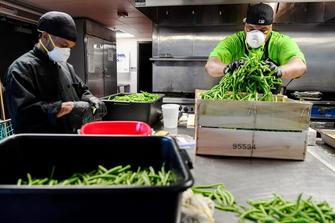Kendrick Burton, left, and Kikkoman Shaw prepare green beans at the Southside Kitchen in Asheville April 16, 2020.