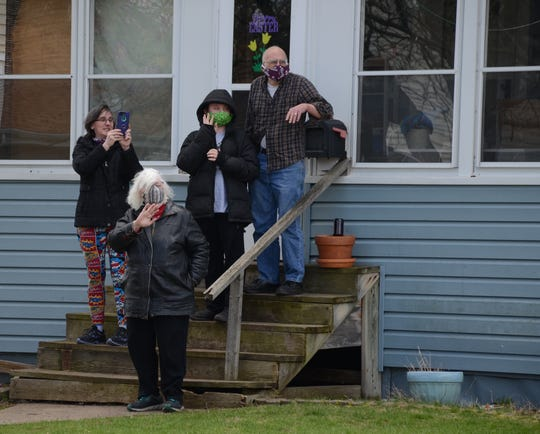 Ian Lockmiller, 11, center, with his family as Battle Creek police pass his home to give him birthday wishes on Thursday.  Trace Christenson/The Enquirer