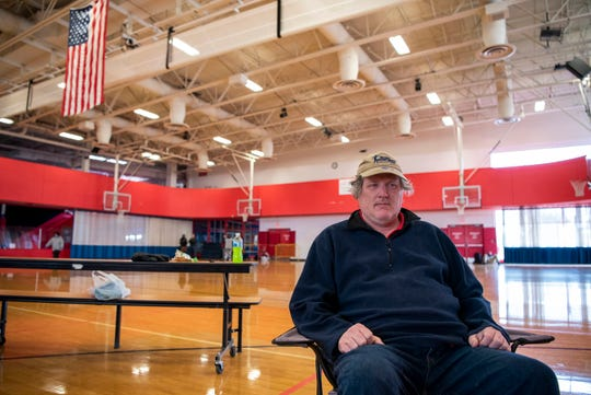 Gerald Croissant watches a movie at Full Blast's indoor recreational center on Wednesday, April 15, 2020 in Battle Creek, Mich. Battle Creek's S.H.A.R.E. Center has converted Full Blast into temporary shelter for homeless citizens during the COVID-19 pandemic.