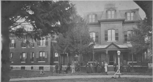 The rear of the Alms House, with several of the poor house inmates, about 1890.