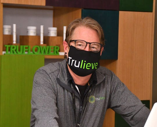 Scott Solary, brand manager, wears a Trulieve face mask inside the company's new dispensary on Columbia Boulevard in Titusville.