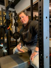 "Sitting on a weight bench, owner Joey Besl talks about how the COVID-19 pandemic has upended his Shelburne gym, Premier Strength and Performance, on Wednesday, April 15, 2020.  Business was booming for Besl, owner of Premier Strength & Performance, who had plans to expand later this year. Then, the COVID-19 pandemic began. ""This is a business, what you put in is what you get out — it's the same with the service we provide,"" Besl said. ""But we can't put anything into it."""