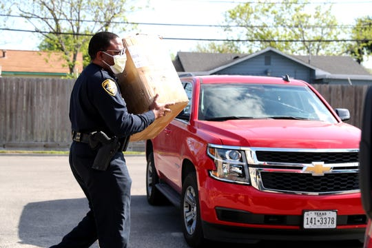 Corpus Christi Police Deputy ChiefAnthony Sanders loads masks donated to the fire department and police department by the Texas Bridge Credit Union on Thursday, April 16, 2020.