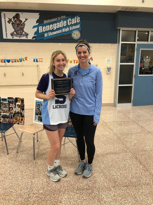 Shawnee's Sami MacDonald, left, stands with coach Julie Cancila after being awarded the No. 22. The number belonged to Katie Kernan, who passed away from brain cancer in 2014.