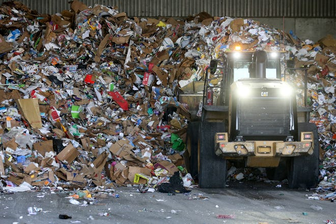A Rumpke worker collects recyclable paper and cardboard products, Thursday, April 16, 2020, at the company's recycling center in St. Bernard, Ohio.